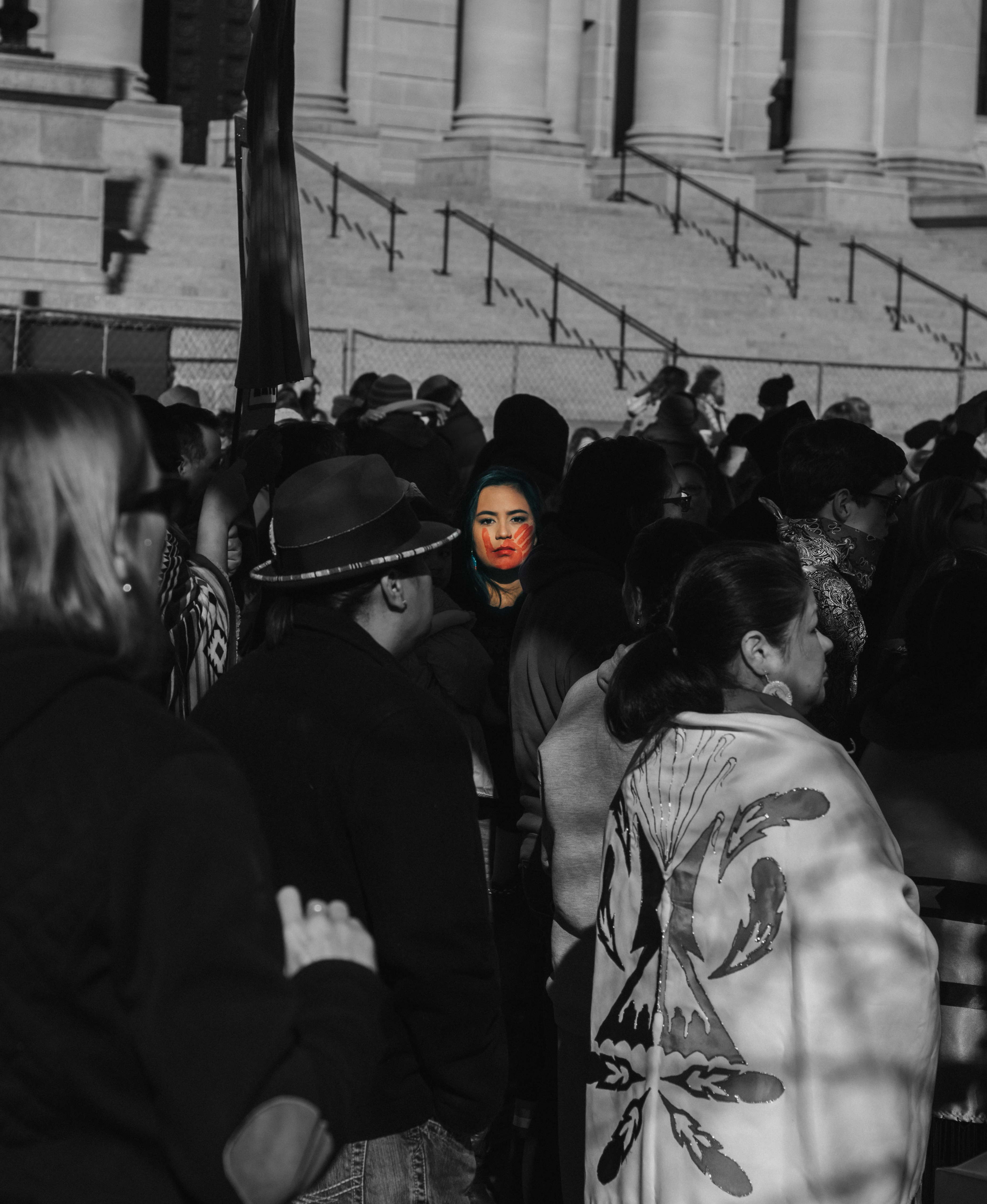 "A Native woman standing in a crowd staring at the viewer. On her face is a red handprint. All others in the crowd are facing away and in black and white. ""The Silenced Sister"" by Cody Hammer, member of the Cherokee Nation and descendant of the Muskogee Creek Nation."