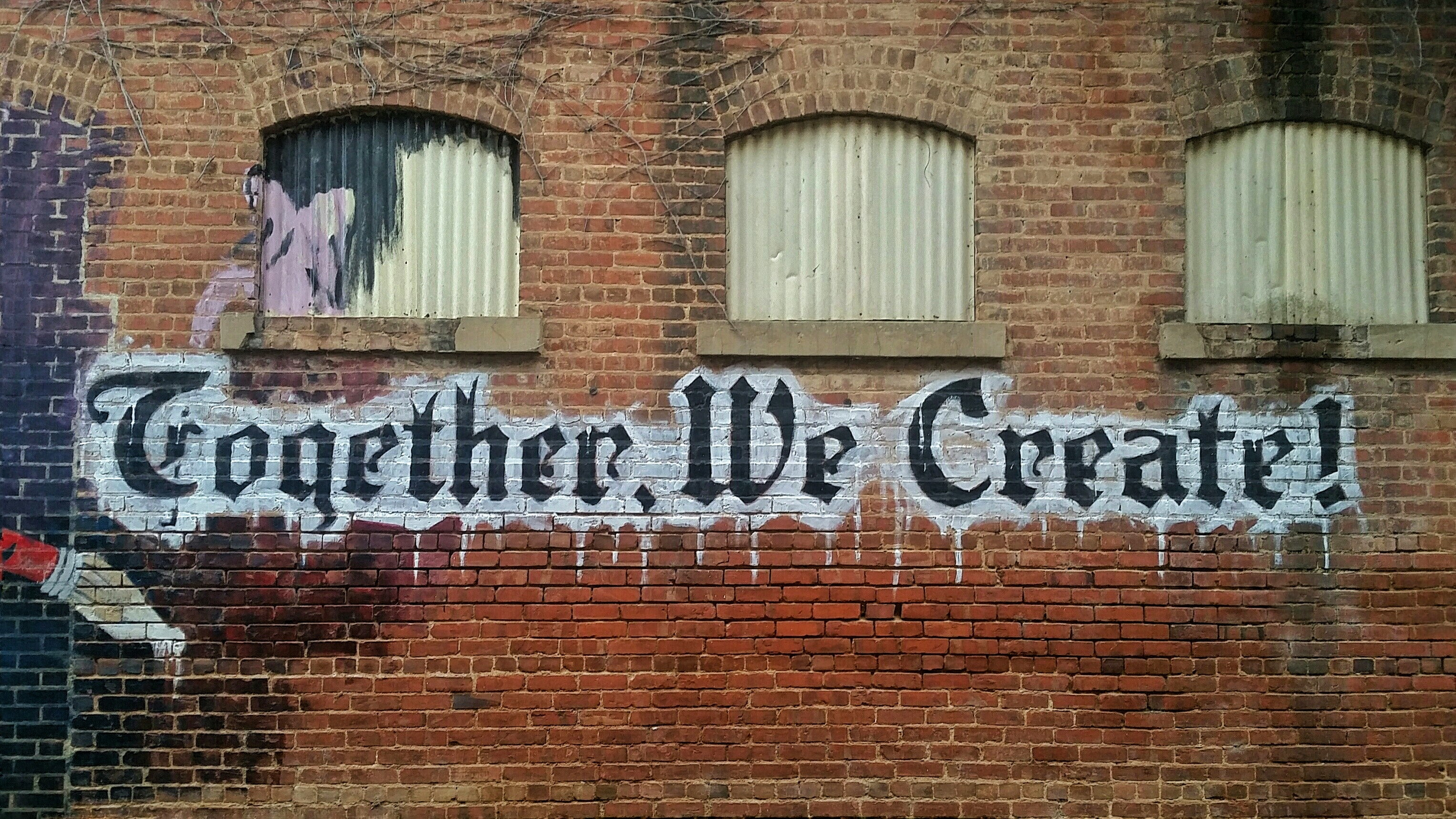 "White and black letter ""Together We Create"" in graffiti style on a brick wall"