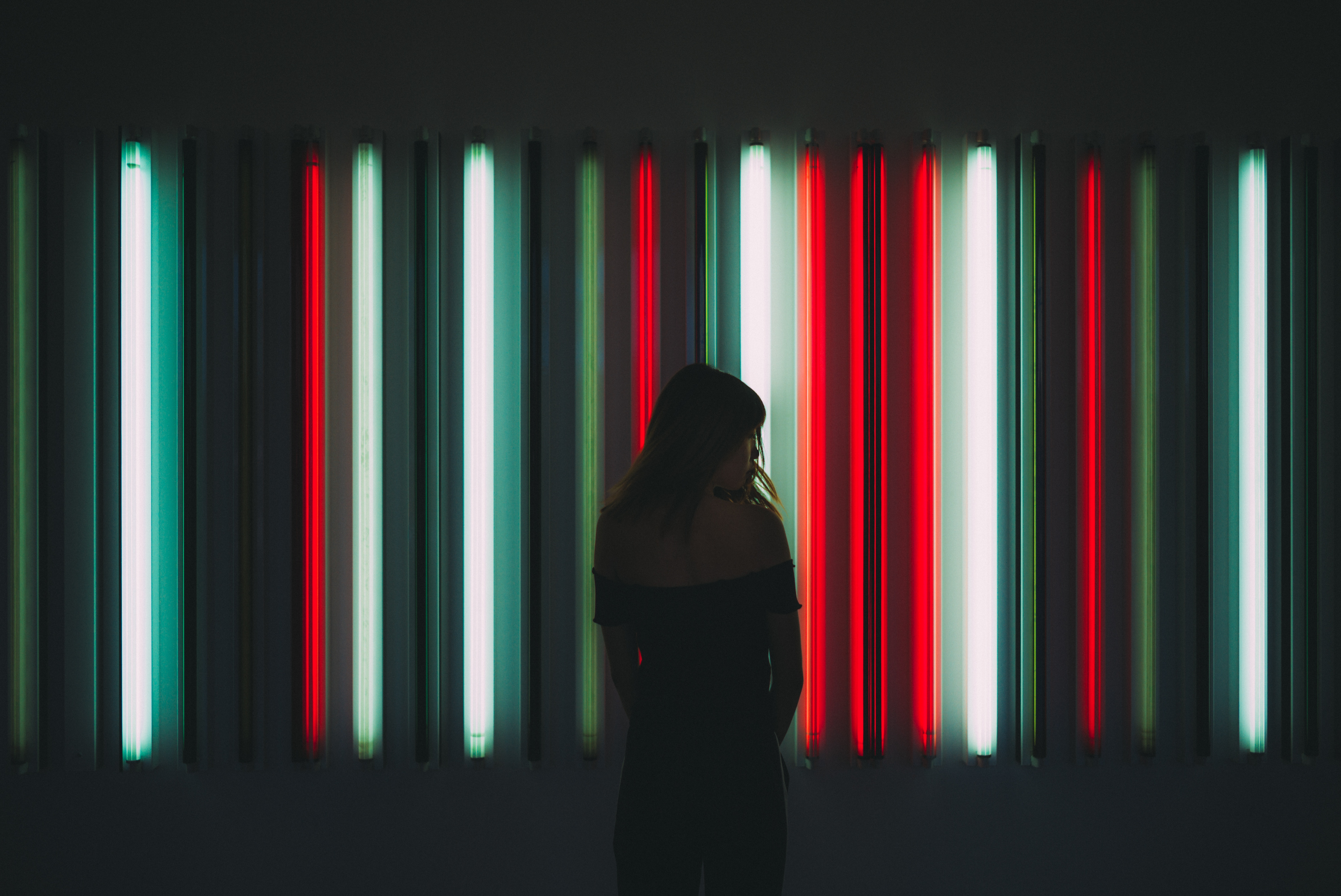 Silhouette of a person standing in front of wall of different colored light bars.